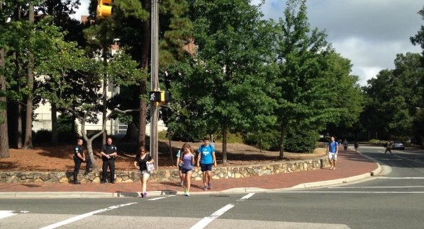 Chapel Hill police officers Drew Cabe (left) and Michael Castro monitor the intersection at South and Raleigh Street on the UNC campus. Police are encouraging pedestrians, bicyclists and motorists to obey traffic laws through the North Carolina Department of Transportation campaign, Watch for Me NC. (Photo by Tatiana Quiroga)