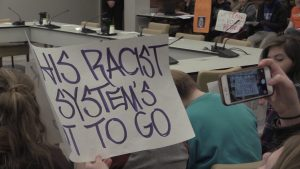 A protester displays a sign at January's UNC Board of Governors meeting. (Photo by Elise McGlothian)