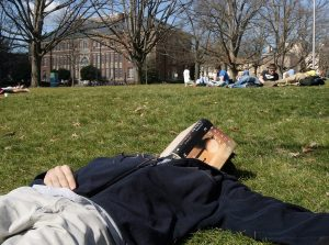 A student naps in Polk Place. (Photo by the UNC Office of Communications and Public Affairs)