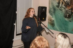 UNC sophomore Elinor Walker performing stand-up comedy at The Scene Is Dead open mic.