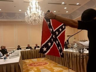 Heather Redding, who is married to a UNC graduate, holds up a confederate flag to the Board of Trustees while voicing her opposition to Silent Sam. (Rachel Bridges/Carolina Connection)